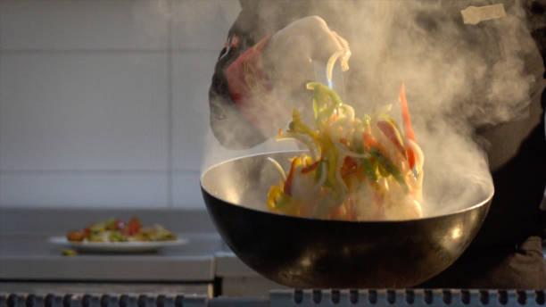 kocken flambaying grönsaker - frying pan bildbanksfoton och bilder