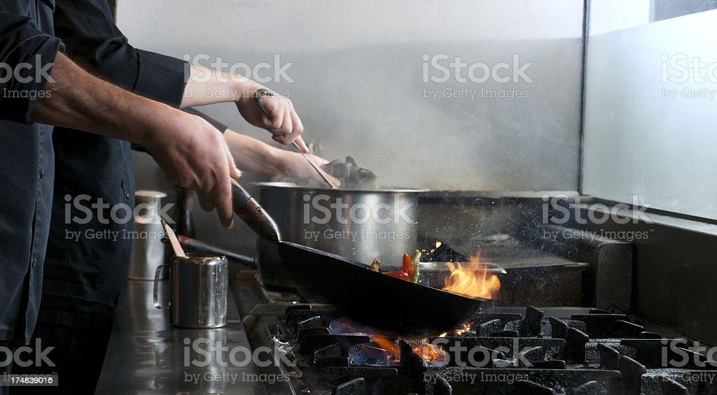 chef flambe vegetables in restaurant kitchen stock photo
