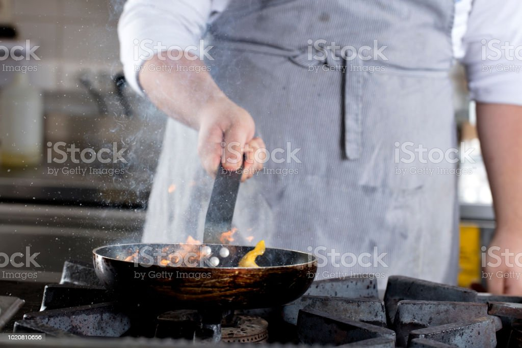 Chef flaming food. stock photo