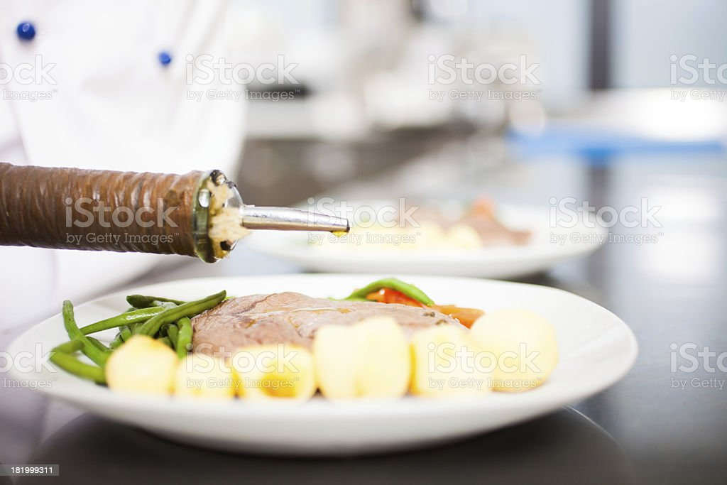 Chef flavoring a dish royalty-free stock photo