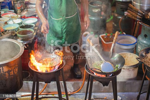 Chef fries in a wok on the vast flame of the stove with rising steam at a street restaurant outdoors in an alley adjacent to Yaowarat Road, the main artery of Chinatown of Bangkok, Thailand, famous with its Thai, Chinese and Thai-Chinese street food.