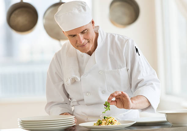 Chef Garnishing Dish In Commercial Kitchen stock photo