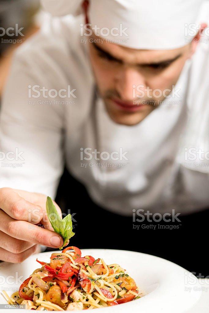 Chef garnishing pasta stock photo