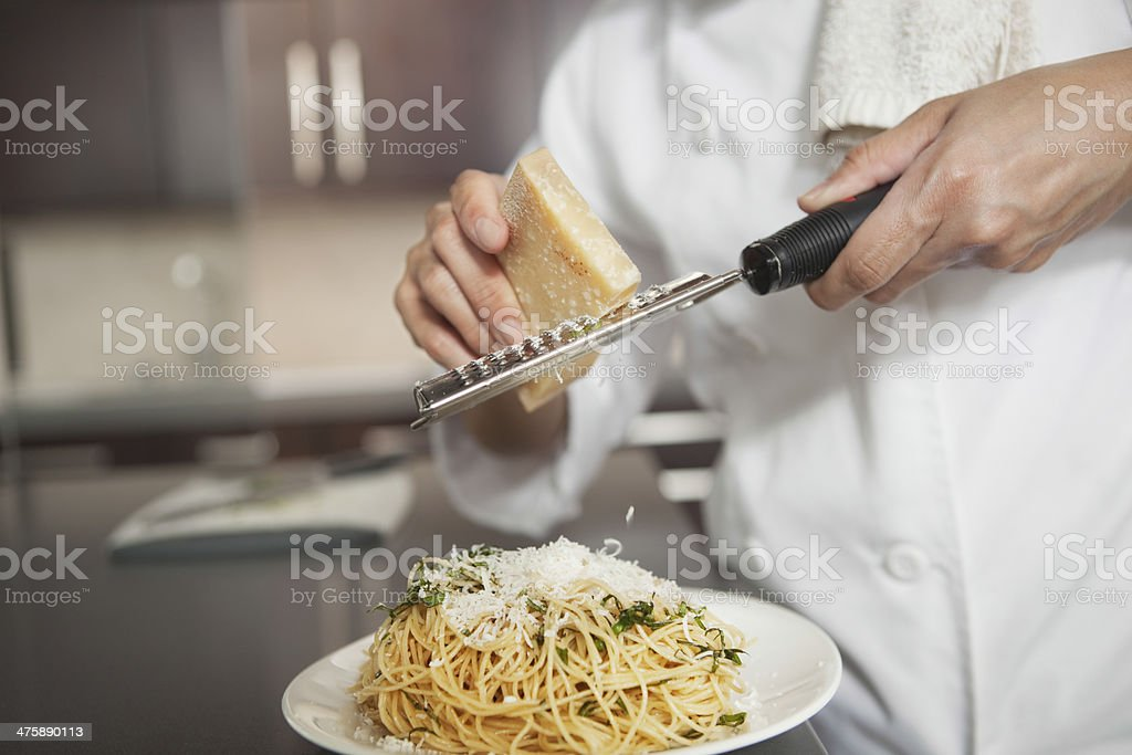 Chef Grating Cheese Onto Pasta In Kitchen stock photo