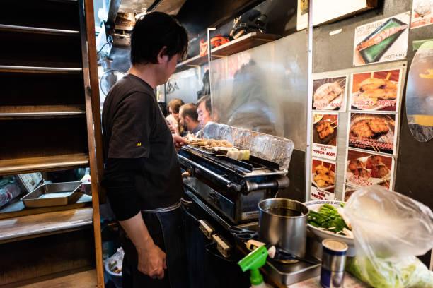 chef grillen spießhuhn, schweinefleisch und rindfleisch in izakaya in memory lane gasse n tokyo in der nacht - kücheneinrichtung nostalgisch stock-fotos und bilder