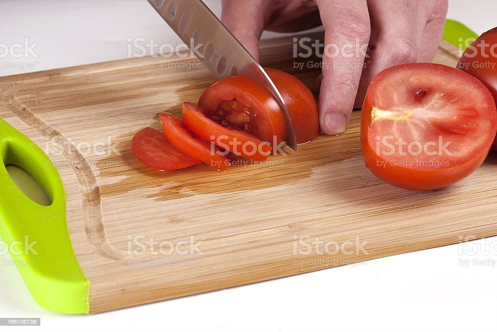 Chef Hand and Knife Slicing Tomato royalty-free stock photo
