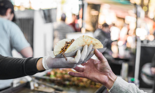 Chef handing a taco to a foodie at a street food market Customer taking their food at a food market food festival stock pictures, royalty-free photos & images