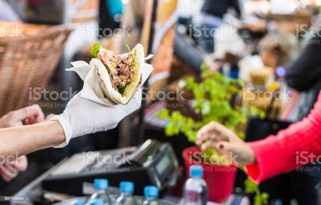 Chef handing a tortilla to a foodie at a street food market stock photo