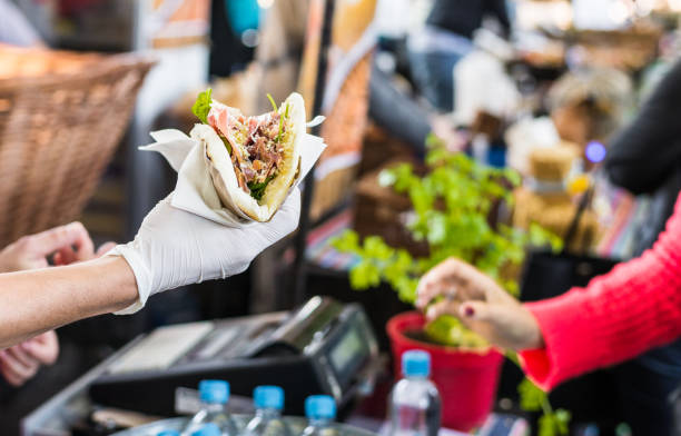 Chef handing a tortilla to a foodie at a street food market Customer taking their food at a food market food festival stock pictures, royalty-free photos & images