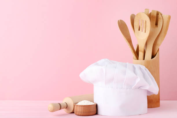 Chef hat with cooking cutlery and flour on pink background Chef hat with cooking cutlery and flour on pink background chef's hat stock pictures, royalty-free photos & images