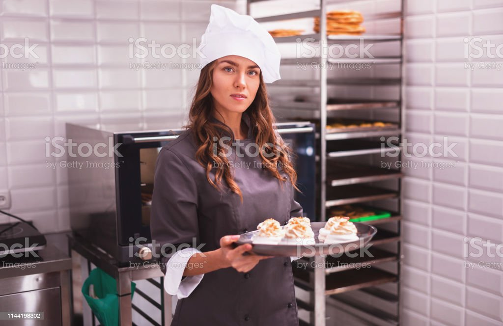 Chef hold sprinkle with cakes. Young cook cooking cakes in the...