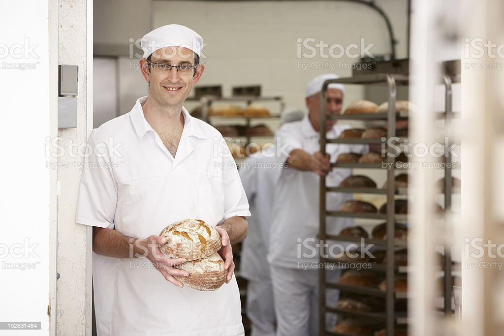 Chef holding loaves of bread in kitchen stock photo