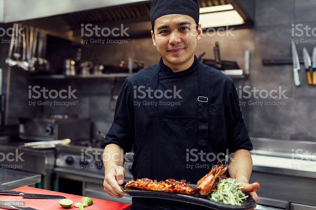 Chef Holding Prepared Meal. stock photo