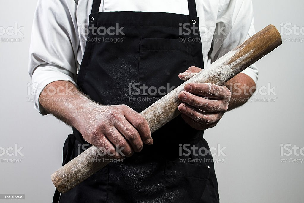 chef holding rolling pin stock photo