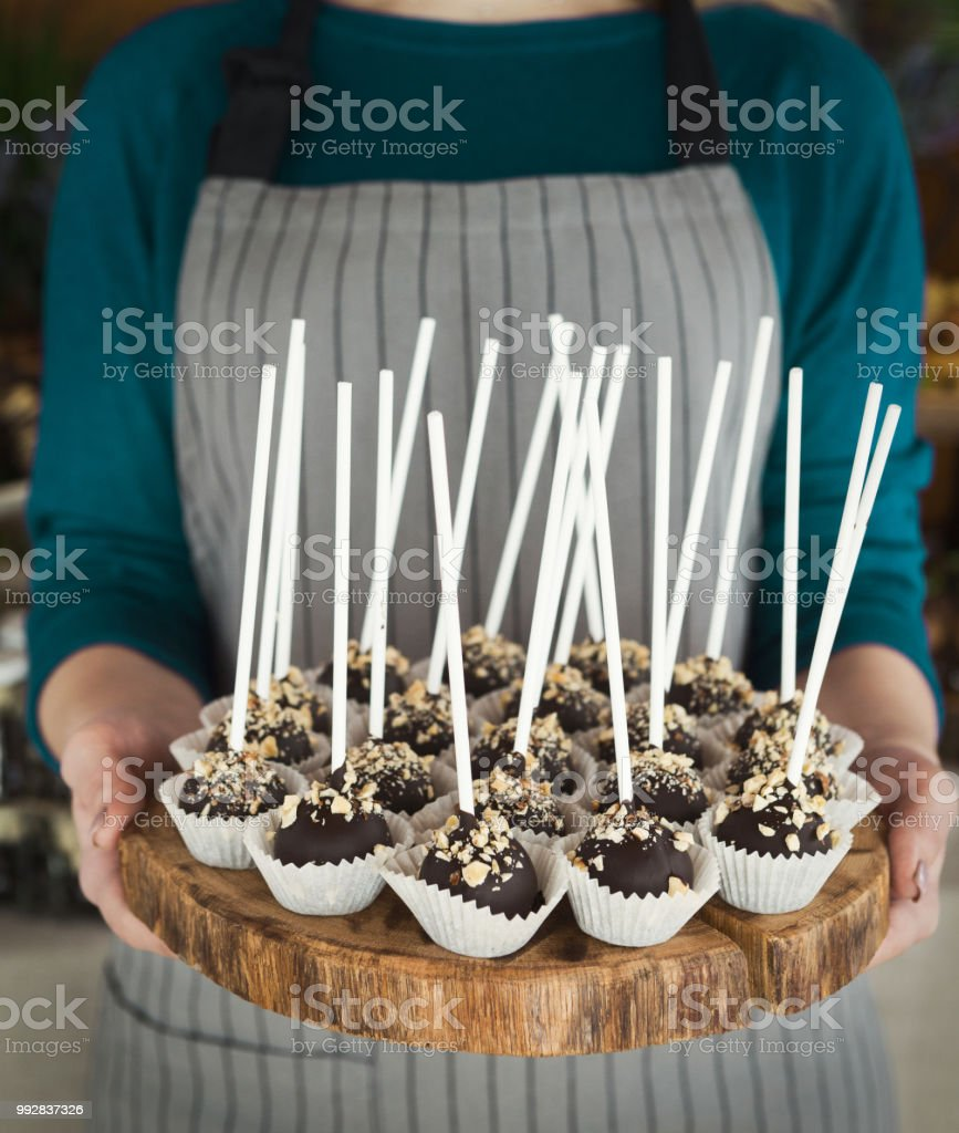Chef Holding Wooden Tray With Chocolate Cookie Pops On Sticks Stock
