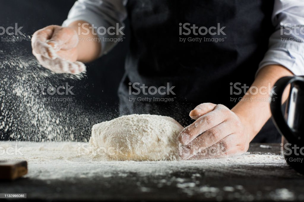 A chef in a black apron sprinkles flour on the kitchen table with flour A chef in a black apron sprinkles flour on the kitchen table with flour side view Adult Stock Photo