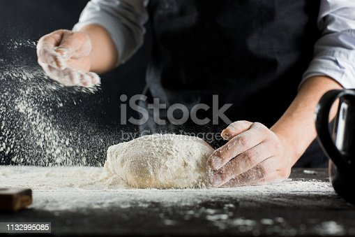 A chef in a black apron sprinkles flour on the kitchen table with flour side view