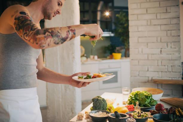 koch in der küche einen teller dekorieren - italienische küchen dekor stock-fotos und bilder