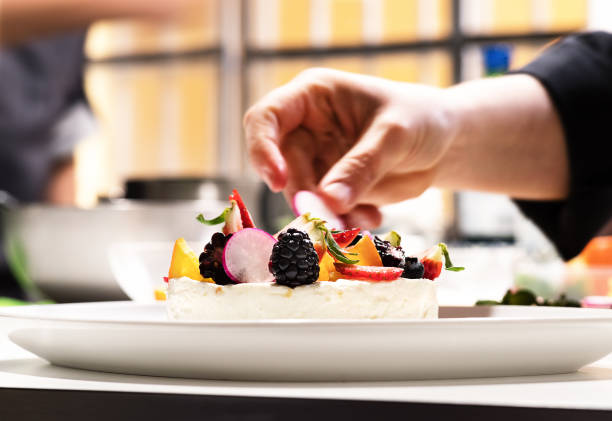 Chef in cuisine makes cheesecake with fruits - foto stock