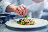 Chef in hotel or restaurant kitchen cooking, only hands. Prepared fish steak with dill decoration