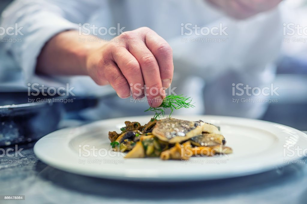 Chef in hotel or restaurant kitchen cooking, only hands. Prepared fish steak with dill decoration stock photo