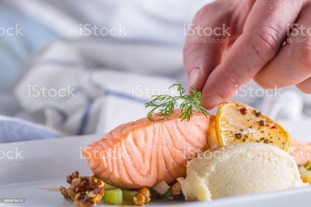 Chef in hotel or restaurant kitchen cooking, only hands. Prepared salmon steak with dill decoration stock photo