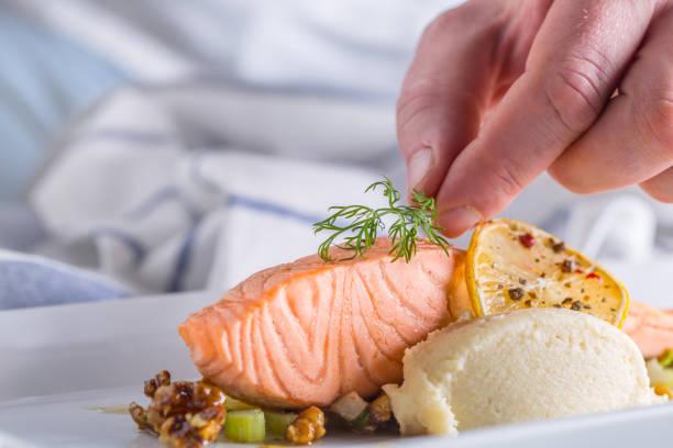 chef no hotel ou restaurante cozinha cozinhando, apenas as mãos. bife de salmão preparado com decoração de endro - fine dining - fotografias e filmes do acervo