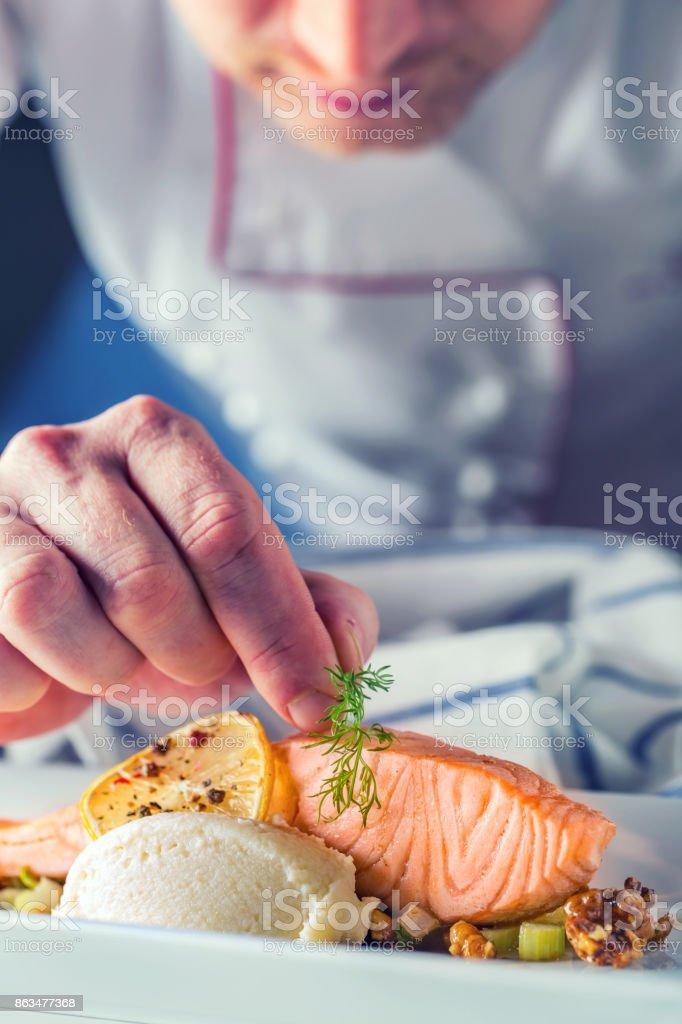 Chef no hotel ou restaurante cozinha cozinhando, apenas as mãos. Bife de salmão preparado com decoração de endro - foto de acervo