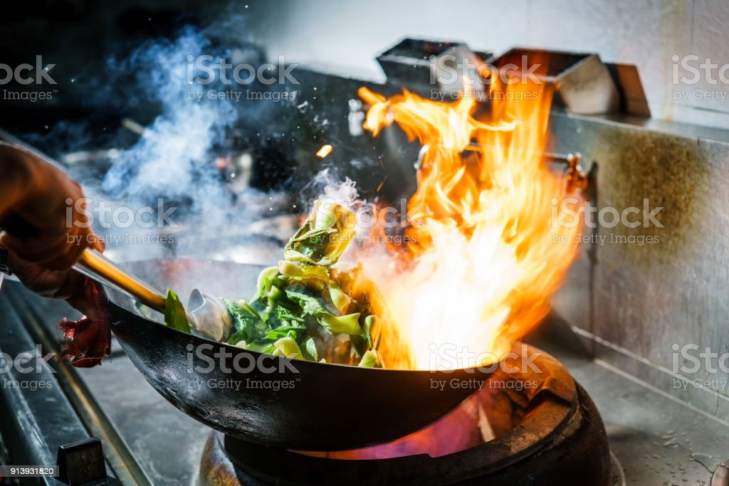 Chef in restaurant kitchen at stove with high burning flames stock photo