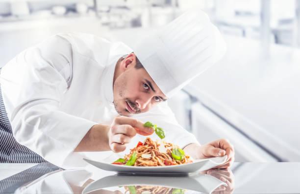 küchenchef im restaurantküche bereitet und schmückt mahlzeit mit händen. koch bereitet spaghetti bolognese - italienische küchen dekor stock-fotos und bilder