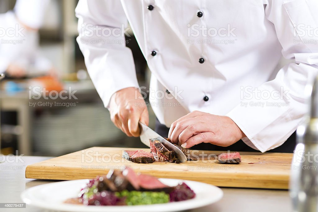 Chef in restaurant kitchen preparing food stock photo