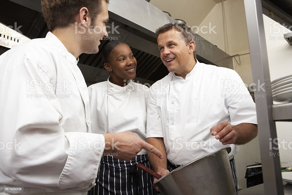 Chef Instructing Trainees In Restaurant Kitchen royalty-free stock photo