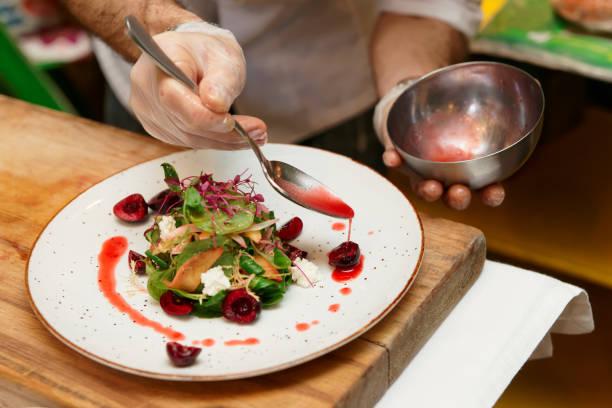 küchenchef ist gemüse vorspeise soße hinzufügen - italienische küchen dekor stock-fotos und bilder