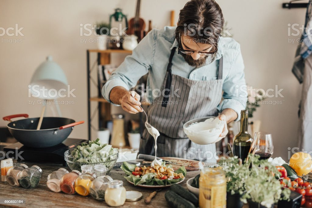 Chef is adding sour cream topping on salad stock photo