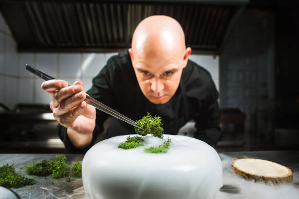 Chef is concentrated on preparing modern molecular dish with pincers and liquid nitrogen stock photo