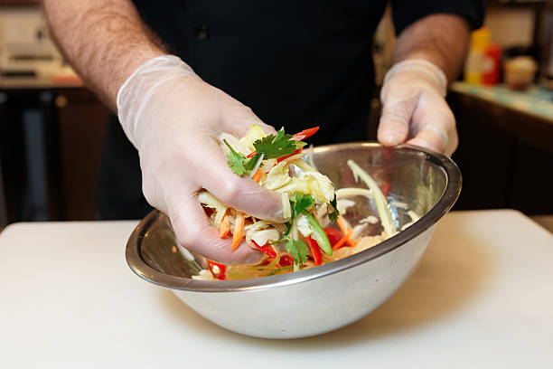 Chef is cooking a vegetarian salad Chef is mixing a vegetarian salad in stainless steel bowl latex stock pictures, royalty-free photos & images