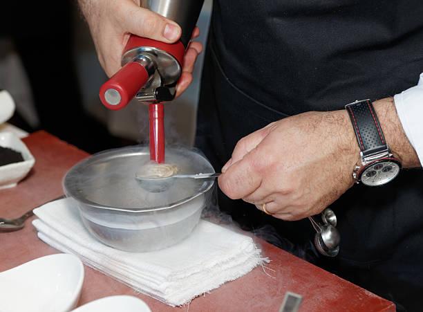 chef kocht eis mit flüssigem stickstoff - crock pot süßigkeiten stock-fotos und bilder