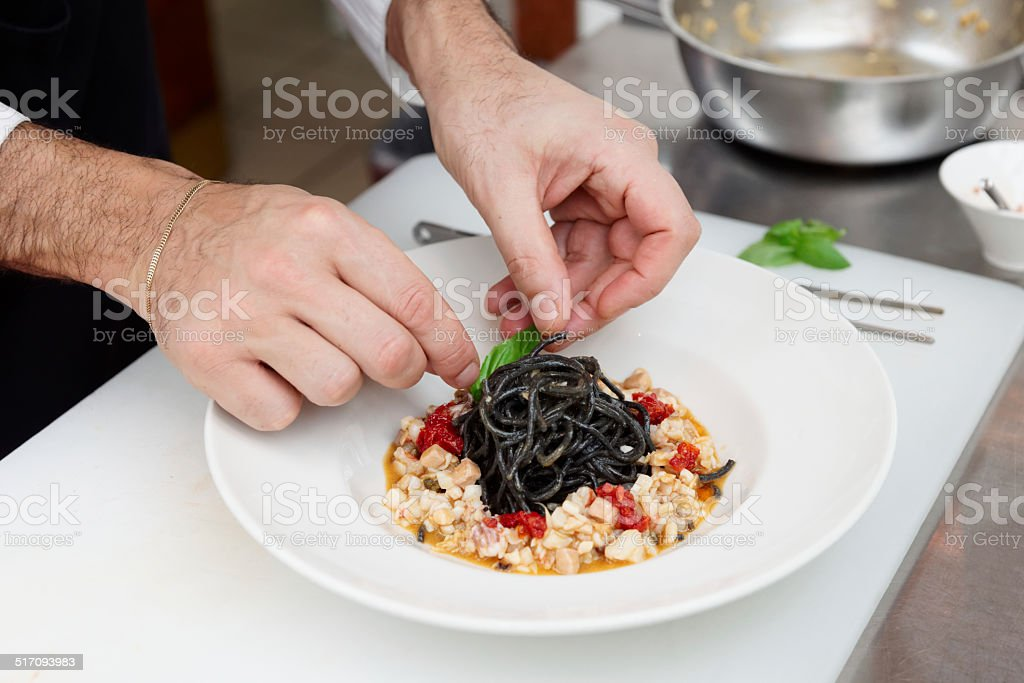 Chef is cooking pasta at commercial kitchen stock photo