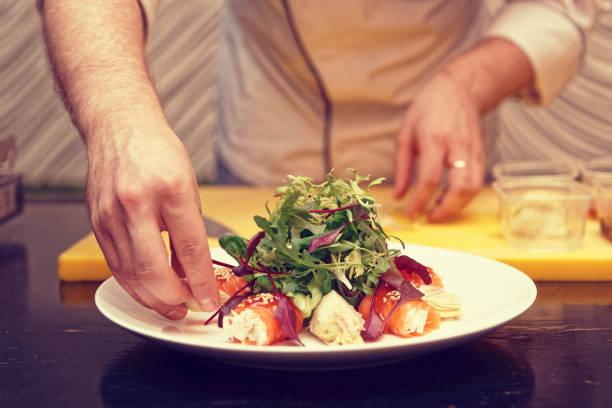 chef kocht lachsbrötchen vorspeise, getönt - italienische küchen dekor stock-fotos und bilder