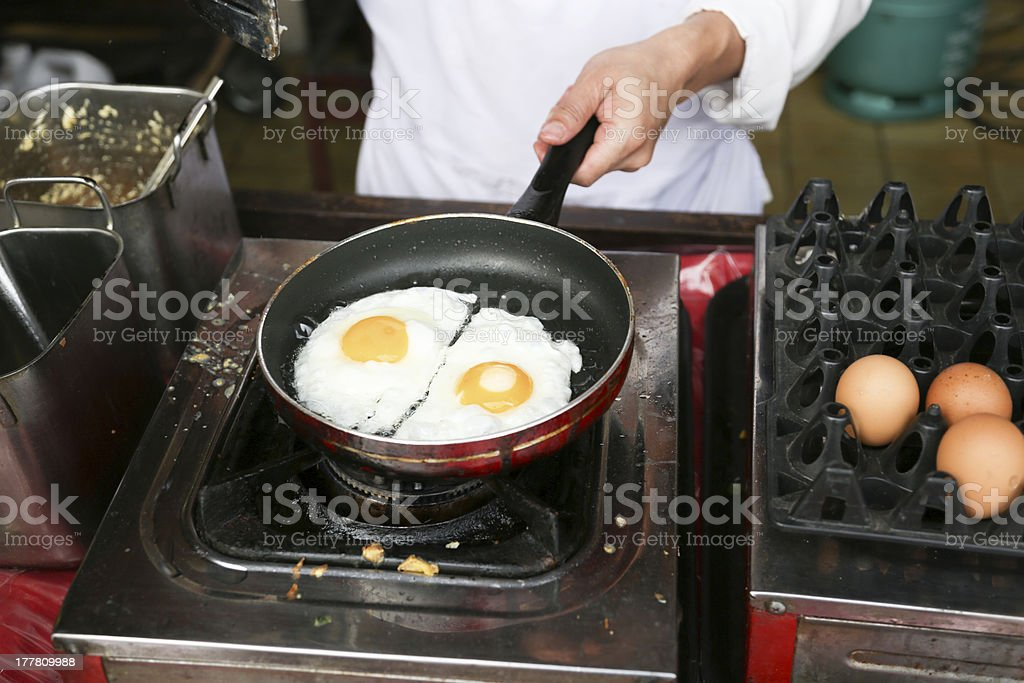 Chef is cooking sunny-side up eggs stock photo