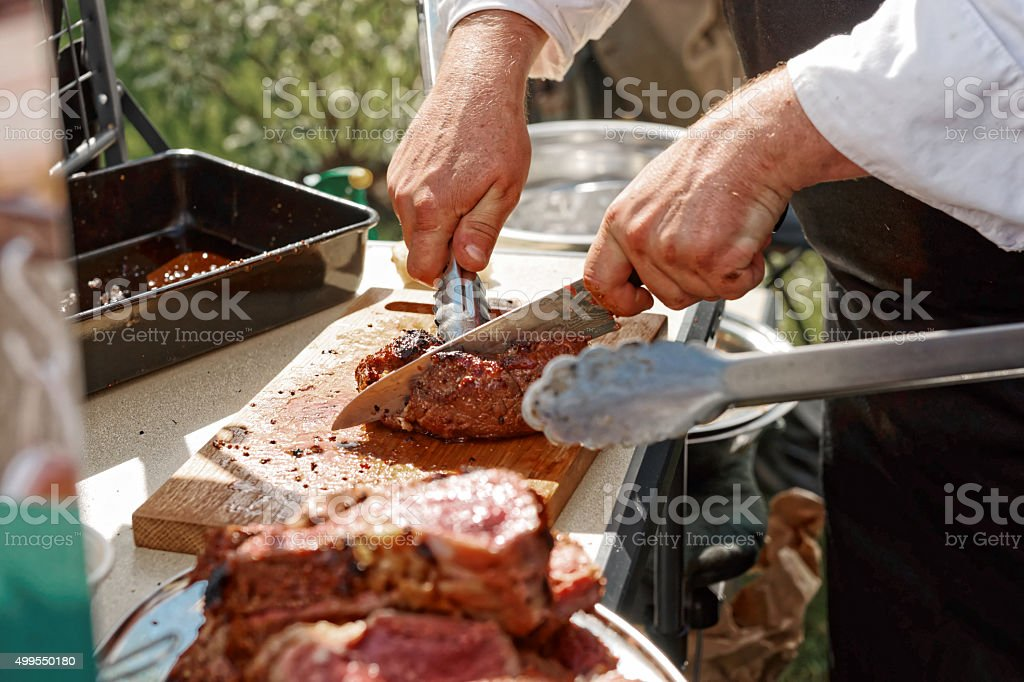 Chef is cutting meat stock photo