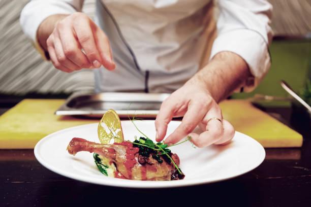 chefkoch dekorieren ein gericht, getönt - italienische küchen dekor stock-fotos und bilder
