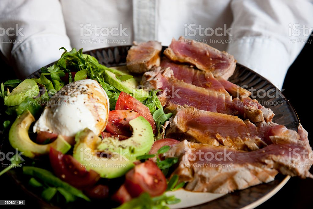 Chef is holding ahi tuna salad stock photo