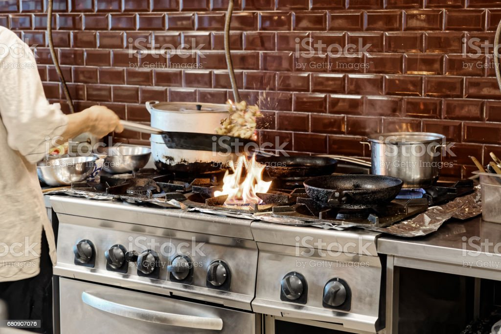Chef is making flambe dish in restaurant kitchen, toned royalty-free stock photo