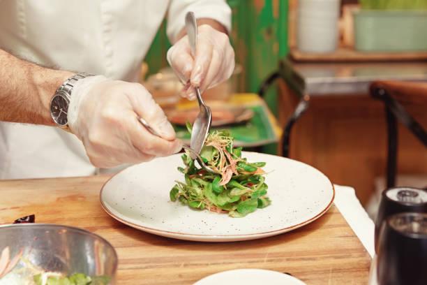 koch macht gemüse vorspeise, getönt - italienische küchen dekor stock-fotos und bilder