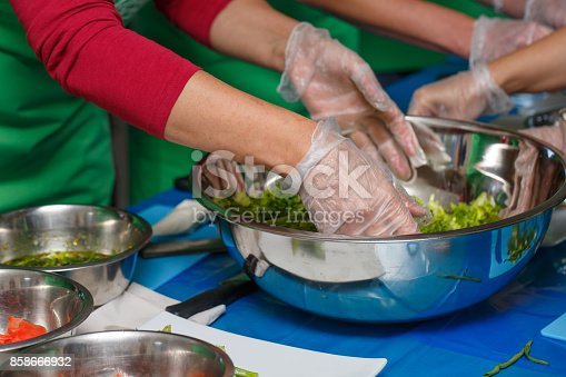 istock Chef is mixing a vegetarian salad in stainless steel bowl 858666932