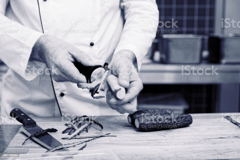 Chef is peeling cucumbers, toned royalty-free stock photo