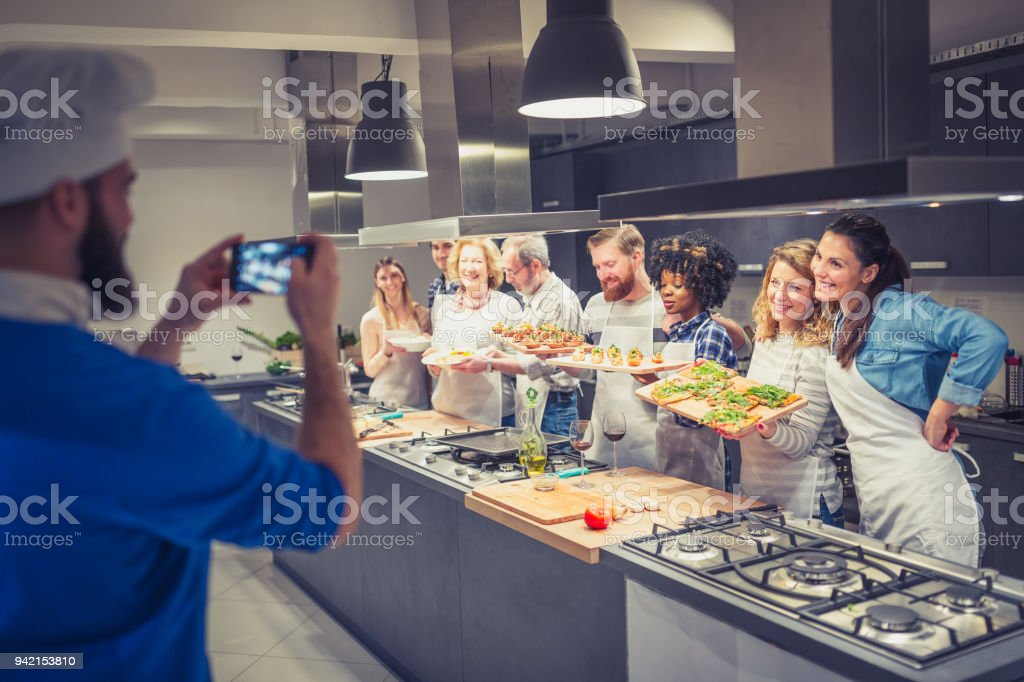 Chef is photographing attendees of cooking class stock photo