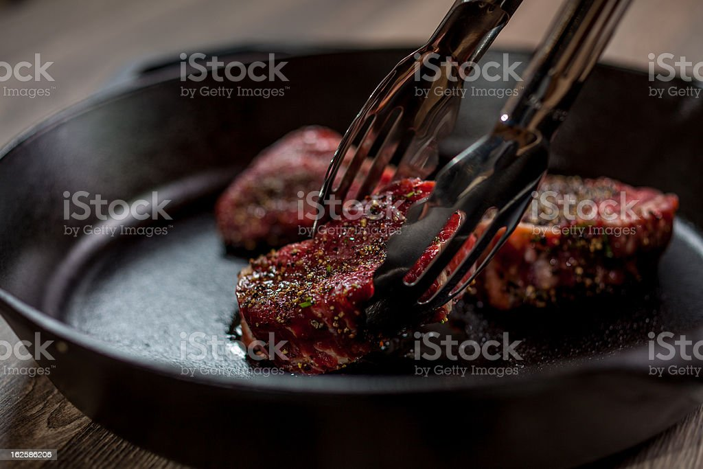 Chef is placing tenderloin steaks with kitchen tongs royalty-free stock photo