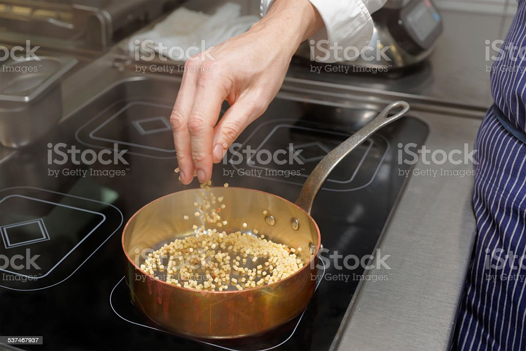 Chef is pouring fregola pasta in pan stock photo